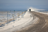 Semi tractor trailer travels down the wintery and snowy James Dalton highway in Alaska's arctic north slope.
