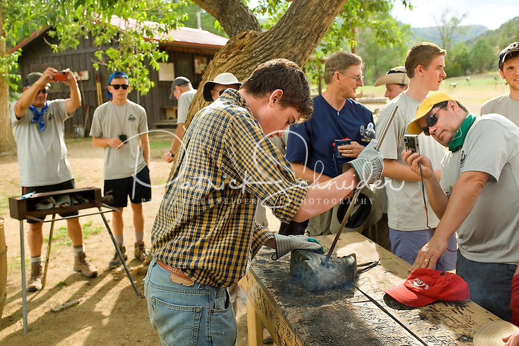 Photo story of Philmont Scout Ranch in Cimarron, New Mexico, taken during a Boy Scout Troop backpack trip in the summer of 2013. Photo is part of a comprehensive picture package which shows in-depth photography of a BSA Ventures crew on a trek. In this photo a BSA Venture Crew watches as Philmont backcountry staffer works to brand a pair of hiking boots. <br /> <br /> Photo by travel photograph: PatrickschneiderPhoto.com