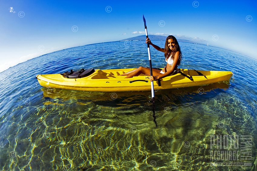 A young woman paddles a kayak in Lahaina, Maui.