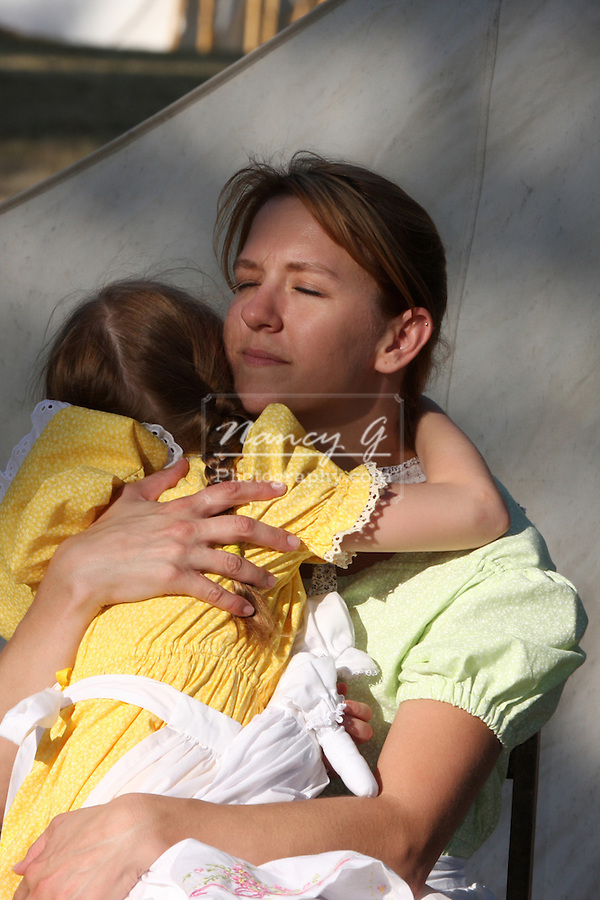 A mother hugging her daughter in historical American clothing
