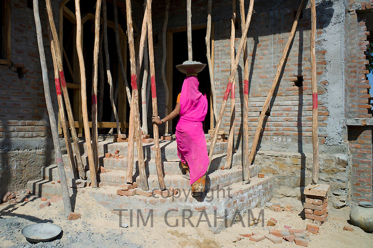 Indian woman in sari carrying cement while working on construction site at Khore village in Rajasthan, Northern India
