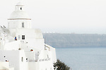 A church sits on the edge of the caldera in the main village of Fira on the island of Santorini in Greece.