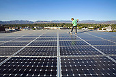 Cleaning Solar panels. Array on rooftop  of office building in Panorama City, San Fernando Valley, Los Angeles, California, USA