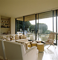 The living area of the beach house has floor-to-ceiling glazed doors with a relaxed seating arrangement in white cotton loose covers