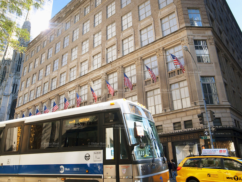 USA. New York City. Yellow cabs and MTA public city buses on 5th Avenue. Saks Fifth Avenue is a luxury American specialty store owned and operated by Saks Fifth Avenue Enterprises (SFAE), a subsidiary of Saks Incorporated (Saks & Company). The retailer is near the top of the line in fashion, selling apparel, cosmetics, jewelry, and shoes from top designers as well as Saks' own private label merchandise. The company headquarters and the company-designated flagship store are in Midtown Manhattan. The New York flagship store accounts for a significant amount of the entire chain's annual revenue. American flags. 25.10.2011 © 2011 Didier Ruef