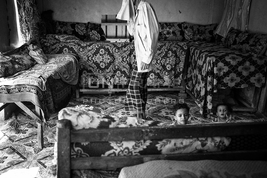 Abdul Salam Yusuf (50), a carpenter from Bayt al-Faqih city, stands in his livingroom with two of his 12 children. His 15 months old son Abdul Majid is malnourished. Two of his older sons (25 and 17) are now working illegally in Saudi Arabia; one is a waiter and the other a carpenter too.<br /> <br /> He and his family are beneficiaries from one of the cash distributions programs that the international aid carries out in Bayt al-Faqih, one of the most impoverished districts in Yemen.<br /> <br /> October 9th 2012.