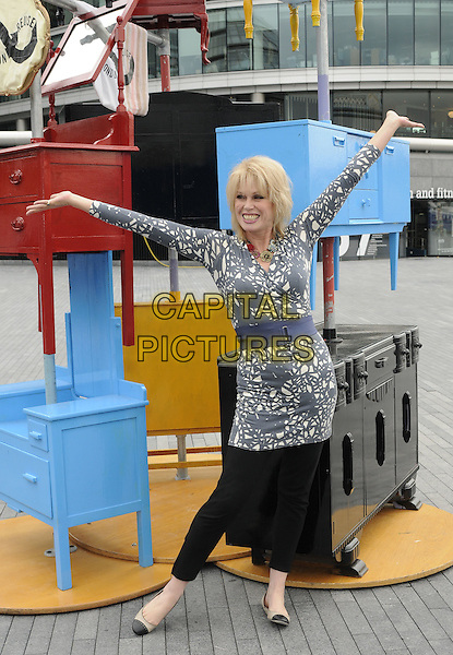 JOANNA LUMLEY  .The launch of the old furniture recycling scheme, The Scoop, More London, the Queen's Walk, London, England..July 12th, 2010.full length black grey gray white print top blue waist belt trousers leggings hands arms outstretched posing dresser chest of drawers.CAP/CAN.©Can Nguyen/Capital Pictures.