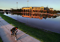 Principal Park, almost completely surrounded by flood water from the Raccoon River, made for a placid backdrop for a bicyclist Friday evening, June 13, 2008.  The Iowa Cubs were to host a game Friday night, but the floods forced a cancellation.