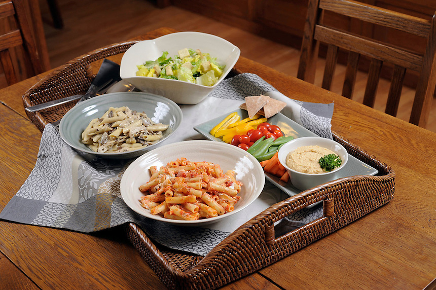 A meal for a family gathering prepared by Linda Mutschler at her Milwaukee home includes vegetables with hummus, baked zitti with ricotta cheese, creamy baked penne with mushrooms and chicken, and a Caeser salad. Table ware by Past Basket. Ernie Mastroianni photo.