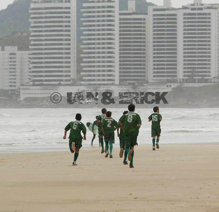 Kids going soccer training on the beach in Guaruja, Brazil.