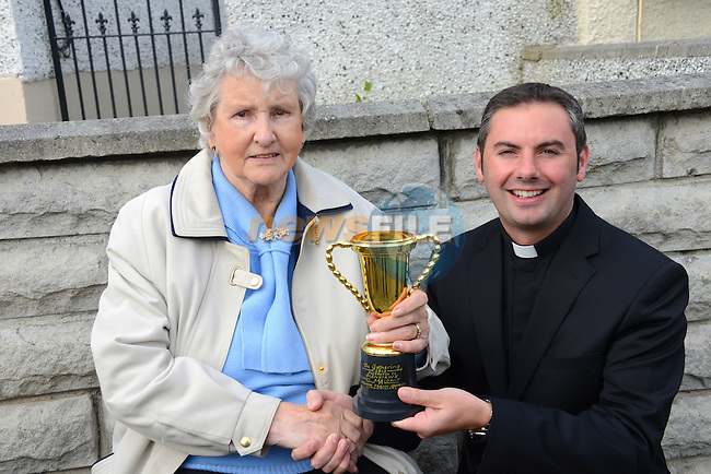 Glenview's oldest resident, 89 year old Margaret Finglas is presented with a commemorative trophy by Fr. Emlyn McGinn at the Glenview 80th anniversary party. Photo: Andy Spearman