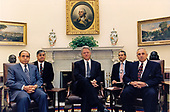 United States President Bill Clinton, center, meets in the Oval Office of the White House with Lieutenant General Hikmat al-Shiabi, Chief-of-Staff of Syria, left, and Lieutenant General Amnon Shahak, Chief of Staff of Israel, right, in Washington, DC on June 29, 1995.  The two unidentified gentlemen are the interpreters.<br /> Mandatory Credit:  Ralph Alswang / White House via CNP