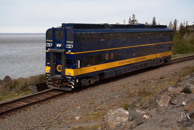 Passenger train in Alaska running by Turnagain Arm, doubledecker Chugach Explorer