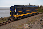 Passenger train in Alaska running by Turnagain Arm, doubledecker Chugach Explorer