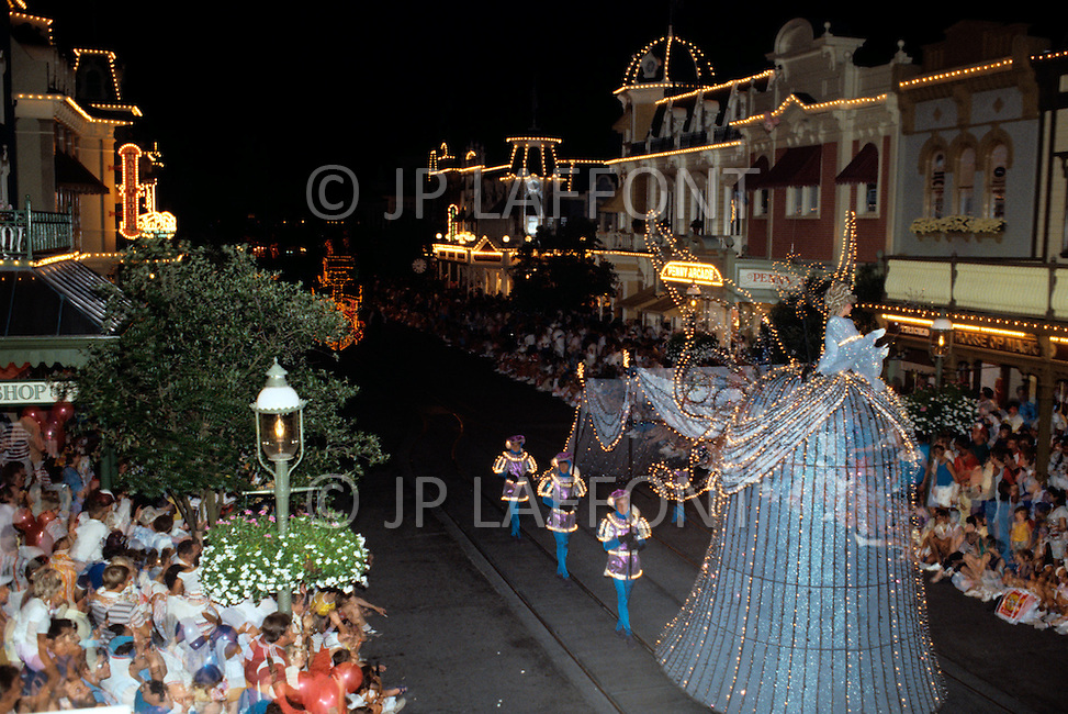 Orlando, Florida - Circa 1986. Disney character greets the audience at the Main Street Electrical Parade. The Main Street Electrical Parade was created by Bob Jani and Ron Miziker, and first appeared at Disney World on June 11, 1977. Disney World is a world-renowned entertainment complex that opened October 1, 1971 in Lake Buena Vista, FL. Now known as the Walt Disney World Resort, the property covers 25,000 acres and has an annual attendance of 52.5million people.