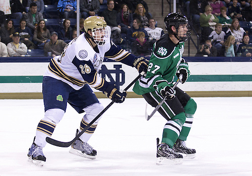 November 23, 2012:  Notre Dame defenseman Stephen Johns (#28) and North Dakota forward Carter Rowney (#27) battle in front of the net during NCAA Hockey game action between the Notre Dame Fighting Irish and the North Dakota Fighting Sioux at Compton Family Ice Arena in South Bend, Indiana.  North Dakota defeated Notre Dame 2-1.
