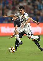 CARSON, CA - SEPTEMBER 15: Joe Corona #14 of the Los Angeles Galaxy attempts to past Matt Besler #5 of Sporting Kansas City during a game between Sporting Kansas City and Los Angeles Galaxy at Dignity Health Sports Complex on September 15, 2019 in Carson, California.