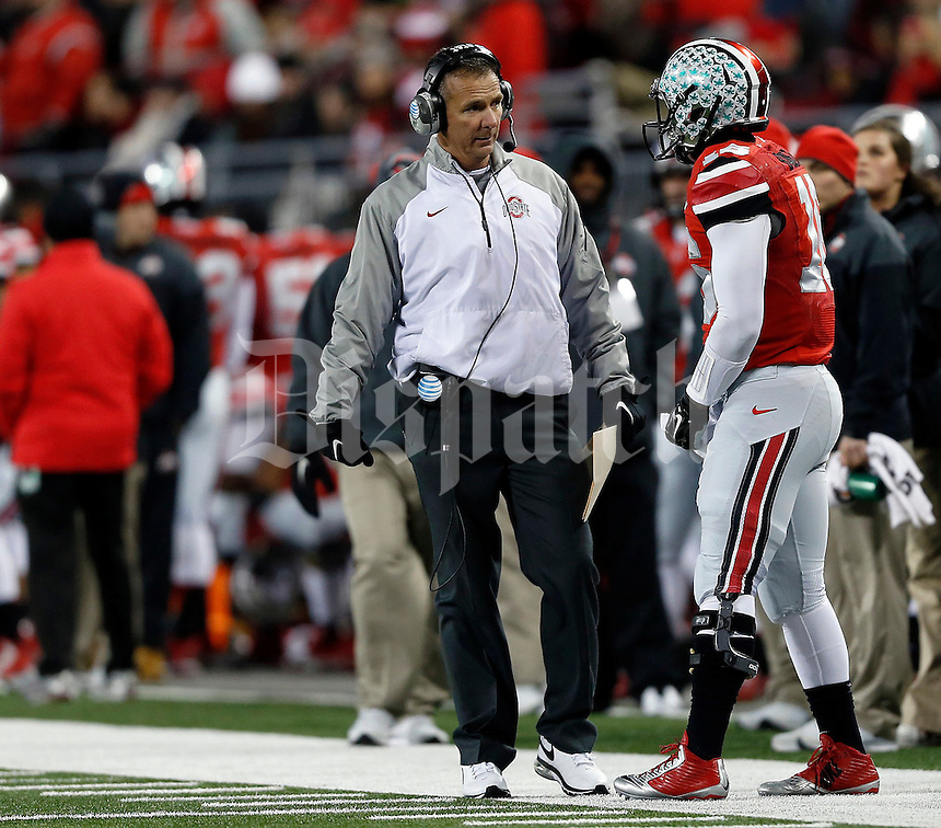 Ohio State Buckeyes head coach Urban Meyer  talks to Ohio State Buckeyes quarterback J.T. Barrett (16) in the first quarter of the NCAA football game at Ohio Stadium on Saturday, November 1, 2014. (Columbus Dispatch photo by Jonathan Quilter)
