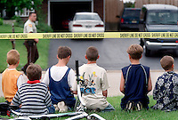 Neighborhood kids sit underneath a police line on Fenney Drive in Plainfield Township, IL waiting for the body of David Yurgil to be brought out of his home. Earlier in the afternoon Yurgil shot his live in girlfriend to death as she fled the house and then  killed himself. (Photo by Robert Sumner)