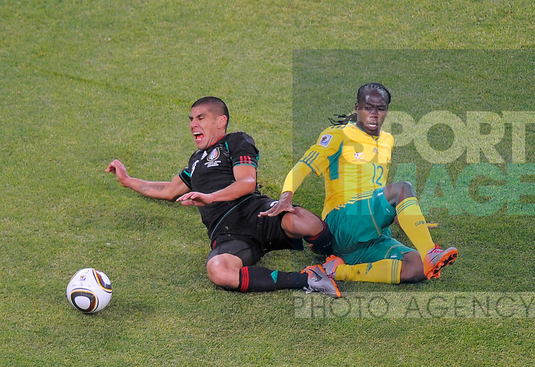 Reneilwe Letsholonyane of South Africa tackles Carlos Salcido of Mexico