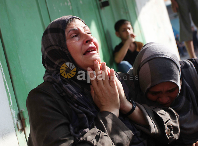 """Palestinians who lost relatives in an Israeli strike on a compound housing a UN school in Jabalia refugee camp in the northern Gaza Strip, mourn outside the Kamal Edwin hospital in Beit Lahia where victims from the attack were brought early on July 30, 2014. Israeli bombardments early on July 30 killed """"dozens"""" Palestinians in Gaza, including at least 16 at a UN school, medics said, on day 23 of the Israel-Hamas conflict.  Photo by Ashraf Amra"""