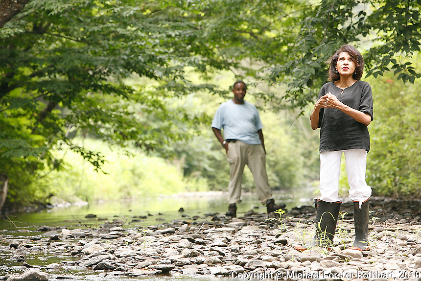 Denise Dennis and her brother Darryl Gore visit their 153-acre family homestead in Hop Bottom, PA. The Dennis Farm has been in the family for seven generations, since their ancestor Prince Perkins became one of the first free blacks to settle in Susquehanna County in 1793. <br /> <br /> Dennis hopes to restore the farm, which includes a family graveyard, original foundations and spring, and an 1859 farmhouse on Martin's Creek. However, uncertainty about natural gas drilling on adjacent properties has made finding funding impossible. Dennis herself sometimes swears she will not lease her land for drilling, but at other times wonders if revenue from gas wells could fund restoration of the property. <br /> <br /> Hydraulic fracturing or &quot;fracking&quot; is new method of drilling for natural gas: millions of gallons of water, sand and proprietary chemicals are pumped down a well under high pressure. The pressure fractures the shale, opening fissures so that natural gas can flow more freely. In August 2010, fracking is being widely used in the Marcellus Shale formation under Pennsylvania while New York considers a moratorium until the environmental effects can be reviewed. <br /> <br /> The 2005 Energy Policy Act exempted natural gas drilling from the Safe Drinking Water Act. Scientists have identified volatile organic compounds (VOCs) such as benzene, ethylbenzene, toluene, methane and xylene that have been found in contaminated drinking water near drilling sites. Other environmental concerns include surface water contamination, air pollution, forest fragmentation, plus human health problems. On the other hand, gas companies and property owners stand to earn up to one trillion dollars in profits from drilling in the Marcellus Shale.<br /> <br /> &copy; Michael Forster Rothbart<br /> www.mfrphoto.com <br /> 607-267-4893 o 607-432-5984<br /> 5 Draper St, Oneonta, NY 13820<br /> 86 Three Mile Pond Rd, Vassalboro, ME 04989<br /> info@mfrphoto.com<br /> Photo by: Michael