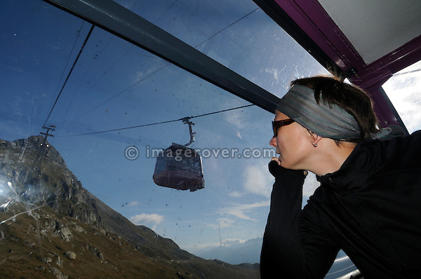 Switzerland, Valais, Western Europe, Aletsch Glacier region (UNESCO world heritage site). Female tourist on the Aerial tramway from Bettmeralp to  Bettmerhorn. --- Model release available.