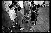 Basketball players of Huazhong Shida First Affiliated High School in Wuhan, Hubei province, check out a damaged hoop before a training session, December 2011.