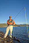 Man fly fishing along the shore of Lake Pleasant in Arizona