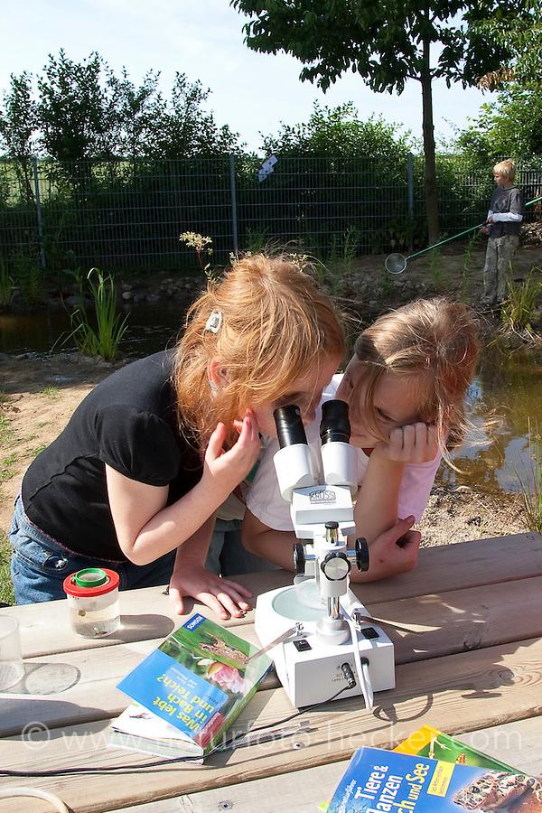 Grundschulklasse, Schulklasse im Schulgarten an ihrem selbst angelegtem Schulteich, Schul-Teich, Gartenteich, Garten-Teich, Kinder haben Tiere aus dem Teich gefangen und beobachten diese im Aquarium und unter einem Binokular, Stereolupe, Exkursion am Teich, Biologie-Unterricht im Freien, Grünes Klassenzimmer