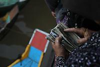 A woman is counting her money at the fish market at Kompong Chhnang, Cambodia-2011