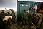 "A U.S. Special Forces operative takes photographs of newly graduated Afghan Public Protection Force guardians, while another records each name, at the squad's checkpoint container in Mayden Shar district, Wardak, Afghanistan, Thursday, May 21, 2009. The 83 graduates of a three-week training course will join 243 others in a grassroots-style pilot program designed to secure communities on the local level. The guardians will return to their own villages to man checkpoints and conduct patrols, in an attempt to deny insurgent ""safe havens"" and extend the reach of the Afghan government. The United States government pays the guardians' salaries and provides vehicles and other equipment and U.S. Special Forces operatives facilitate and support the APPF checkpoints with the Afghan National Police and other Afghan agencies."