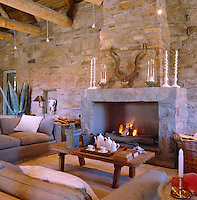 Winters in this remote area of South Africa are cold and under-floor heating supplements the warmth generated by this monumental fireplace in the living room