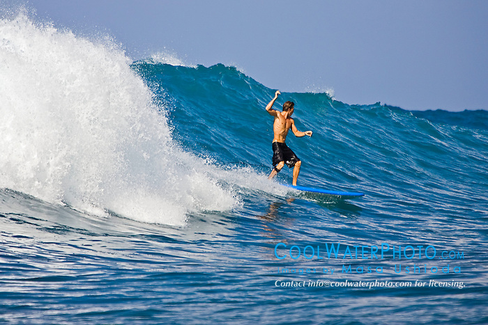 Surfer, enjoying riding rare big ocean waves in Kona Coast, Keauhou Bay, Big Island, Hawaii, Pacific Ocean.