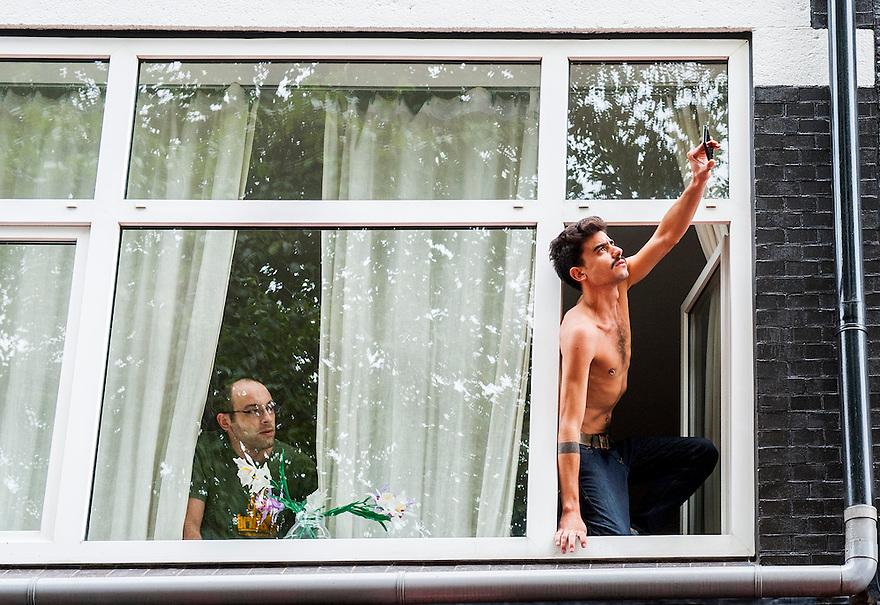 Nederland, Amsterdam, 21 sept 2013<br /> Demonstratie tegen bezuinigingen door het kabinet Rutte2. Half ontklede man met tepelpiercing maakt met telefoon foto's vanuit het raam. <br /> <br /> Foto(c): Michiel Wijnbergh