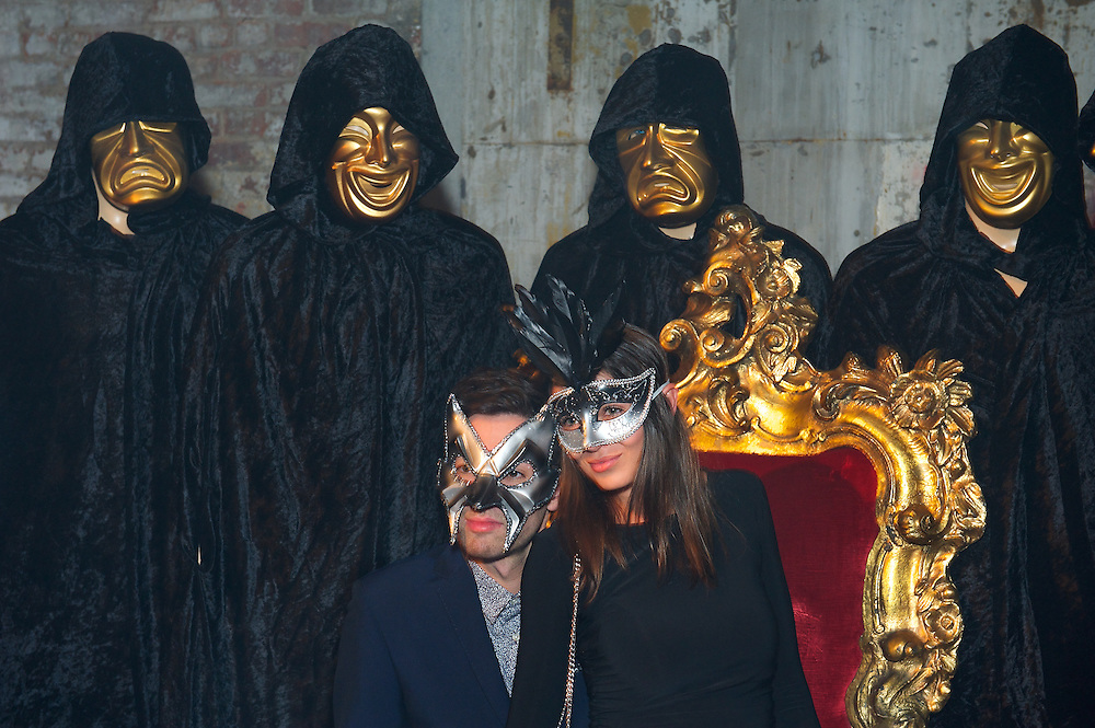 Masked guests posing on red and gold throne at a Halloween party.