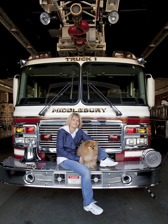 MIDDLEBURY, CT-14 November 2013-111413BF01- Beverly Dassonville poses with her 5-year old Pomeranian Chloe on a Middlebury Fire Department truck Thursday morning. Dassonville is a volunteer E.M.T. with the Middlebury Fire Department Ambulance and created a video that she entered to try to win a $500,000 dog park from the the pet food company Beneful in the Beneful Dream Dog Park Contest.  Bob Falcetti Republican-American