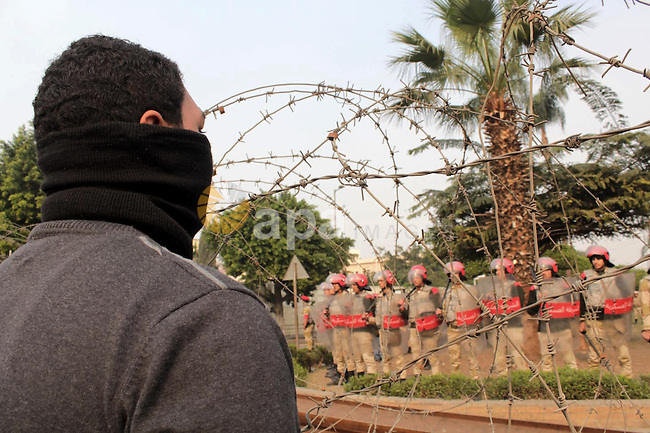 An Egyptian student and supporter of ousted president Mohamed Mursi faces Egyptian army soldiers during a protest near the Ministry of Defense building in Cairo December 18, 2013. Egyptians will vote on a new constitution on Jan. 14 and 15, pushing on with the army-backed government's plan for transition back to democracy after its overthrow of elected Islamist President Mursi. Photo by Mohammed Bendari
