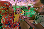 Shortly after they made the perilous crossing from Myanmar into Bangladesh, a woman holds her child as Gius Uddin from Concern checks its health in a United Nations clinic for severely malnourished Rohingya children in the Balukhali Refugee Camp near Cox's Bazar, Bangladesh. He is using a Mid Upper Arm Circumference tape, where the red indicator shows the child is severely malnourished.<br /> <br /> More than 600,000 Rohingya have fled government-sanctioned violence in Myanmar for safety in Bangladesh.