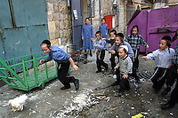 "Orthodox Jewish children chase a chicken in the orthodox neighborhood of Mea Shearim, Jerusalem September 10,2002. Religious Jews perform ""kaparot"" rituals on the days before Yom Kippur. In this Jewish ritual performed ahead of the Day of Atonement, or Yom Kippur, the holiest day in the Jewish year, it is believed that one's sins from the past year are transferred to the chicken. The bird is then slaughtered and given to the poor. (Photo by Quique Kierszenbaum"