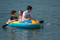 Aberystwyth Wales UK, Thursday 12 May 2016<br /> UK Weather: Three young people in an inflatable dinghy in the sea at the seaside in  Aberystwyth, on the Cardigan Bay coast of west Wales, enjoying a last day of warm weather in the current mini-heatwave. <br /> The temperatures are set to fall over the coming days, with bright but colder conditions prevailing over the country