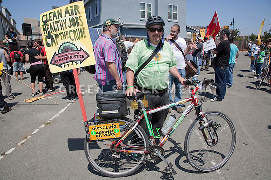 August 15, 2009. Tian Carter of Mountain View bicycles against oil wars. About two hundred people participated in a rally, march, and demonstration protesting Chevron's Richmond oil refinery renovation and expansion project. The event was organized by Mobilization for Climate Justice-West, a coalition of over thirty organizations, working to bring awareness to the refinery issue as well as the United Nations Climate Change Conference taking place in December in Copenhagen. Event organizers claim that the Richmond refinery project will allow the facility to refine heavier and dirtier crude that will result in more air pollution, greenhouse gas (GHGs) emissions, and health risks. A court ruling recently put the refinery project on hold saying that further environmental impact reporting was needed. Many protesters were also concerned about the environmental and human health impacts of oil company projects outside the United States. Richmond, California, USA