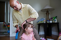 Fred Bermont gets daughter Elyse Bermont (age 2.5) ready for the day by getting her dressed and brushing her teeth in their home in Lexington, Massachusetts, USA, before he goes to work and drops the kids off at day-care on June 9, 2014. Bermont is the father of two children and shares parenting duties with his wife, Jen Bermont. Fred usually takes care of the morning routine, including feeding, dressing, and dropping the kids off at day-care, and Jen picks them up and watches over them in the afternoon. Fred is a Senior Clinical Standards Specialist at Shire, a pharmaceutical company with headquarters in Lexington.