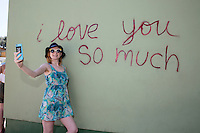 "An Austin local takes a selfie at the famous ""I love you so much"" mural in South Congress, Austin, Texas - Stock Image."