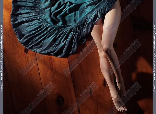 Sensual artistic portrait of sexy woman legs and a green dress on wooden floor