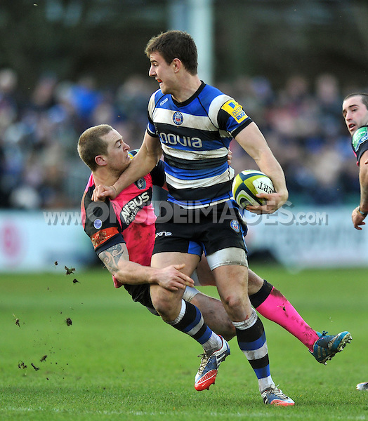 Ollie Devoto shrugs off the tackle of Owen Williams. LV= Cup match, between Bath Rugby and Cardiff Blues on January 25, 2014 at the Recreation Ground in Bath, England. Photo by: Patrick Khachfe / Onside Images
