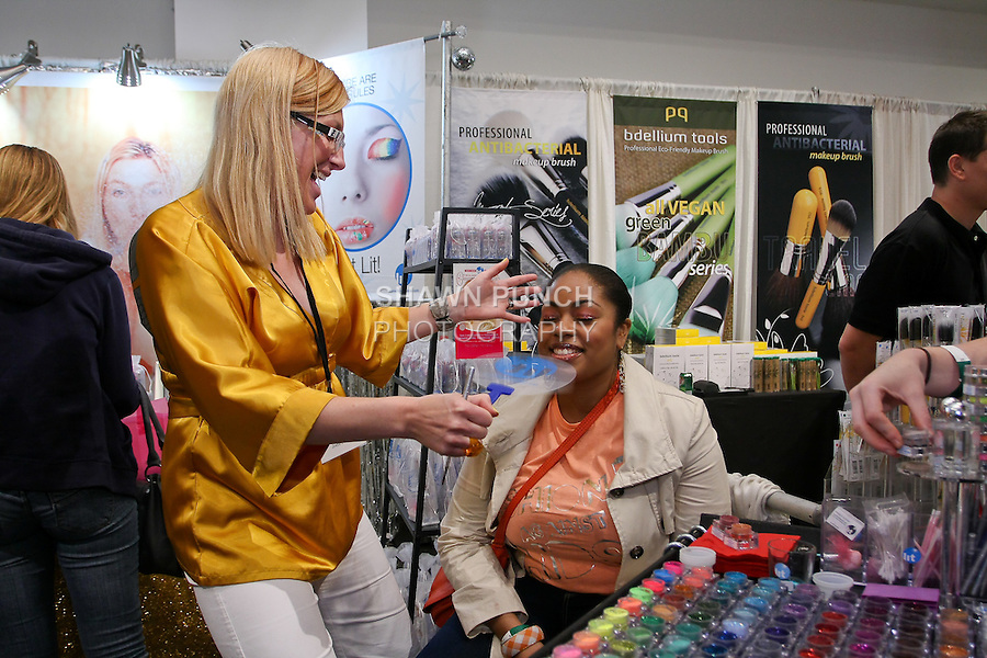 Lit Cosmetics owner/inventor Jodie Perks, applies makeup on woman at the Makeup Show NYC, in the Metropolitan Pavilion, May 15 2011.