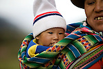 A Peruvian mother wearing traditional clothing smiles as she carries her baby on her back in a rural area near Cuzco, Peru.