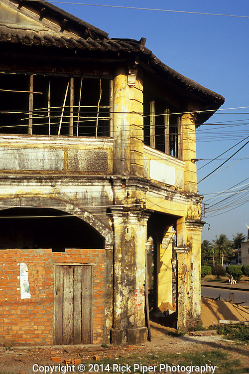 Weathered decaying facade of old French colonial building in the centre of Kampot, Cambodia.
