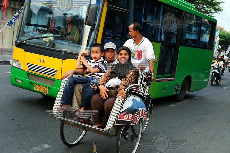 A family ride a padicab or Becak through Yogyakarta.